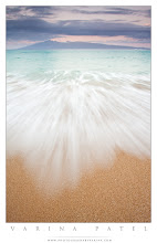 Photo: For the Love of the Islands  #PhotographyTips, #Travel, #Hawaii  Waking up to this? Priceless.  This is the view of the island of Molokai from Napili Bay on Maui. It's not difficult to get out of bed when you are in a place like this. :) You want to get up and get out in the fresh air. We stayed at The Mauian - a beautiful hotel right on the beach - so we just hopped out of bed and grabbed our gear. We were standing on the sand a few moments later, hoping for a crazy sunrise. The brilliant light never materialized - but it's hard to go wrong in a place like this, don't you think?  If you are shooting on the beach, push the legs of the tripod down into the sand so that the waves don't move you around to much. The water was calm this morning - but be careful out there. A sudden, rogue wave can do serious damage to you and your camera gear. The ocean should NEVER be taken for granted. No matter how serene it looks.  Anyway - I wanted to get a shot that showed the motion of the water, and also the changing colors in the scene. The deep purple in the clouds seemed to echo the color of the distant island - and the turquoise water seemed to fade into the white foam and then the beautiful, golden sand.  It is always important to me to remove any distracting elements within the frame in order to keep the image as simple as possible. So my first step is to decide what the image is about. If this shot was going to be about color and motion, then I had to be sure that nothing else would pull your attention from those elements. I moved away from the rocks on the beach, and placed myself close enough to the water that I could avoid the footprints in the dry sand higher on the beach. I pointed my camera straight out toward the Molokai - making sure that none of the palm trees on my left were in the shot. I let the distant island stretch from one edge of my frame to the other. And then I started shooting.  I needed to choose a shutter speed that would be long enough to captu