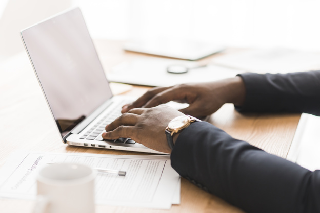 black professional on laptop | Write proposals that get you to the table