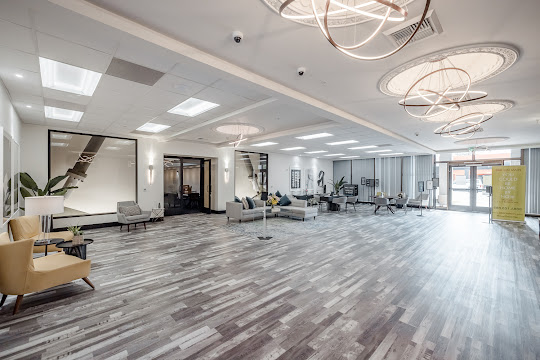 Interior of the clubhouse with wood plank floors, modern chandeliers, several seating areas, and decor throughout