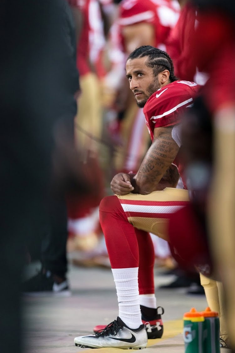 San Francisco 49ers quarterback Colin Kaepernick sits during the national anthem.
