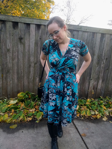 Me in a turquoise palm print Vogue 8379, facing the camera in front of a weathered wooden fence.