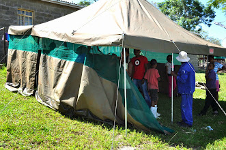 Photo: Erecting tents for storing suitcases outside the girls house.