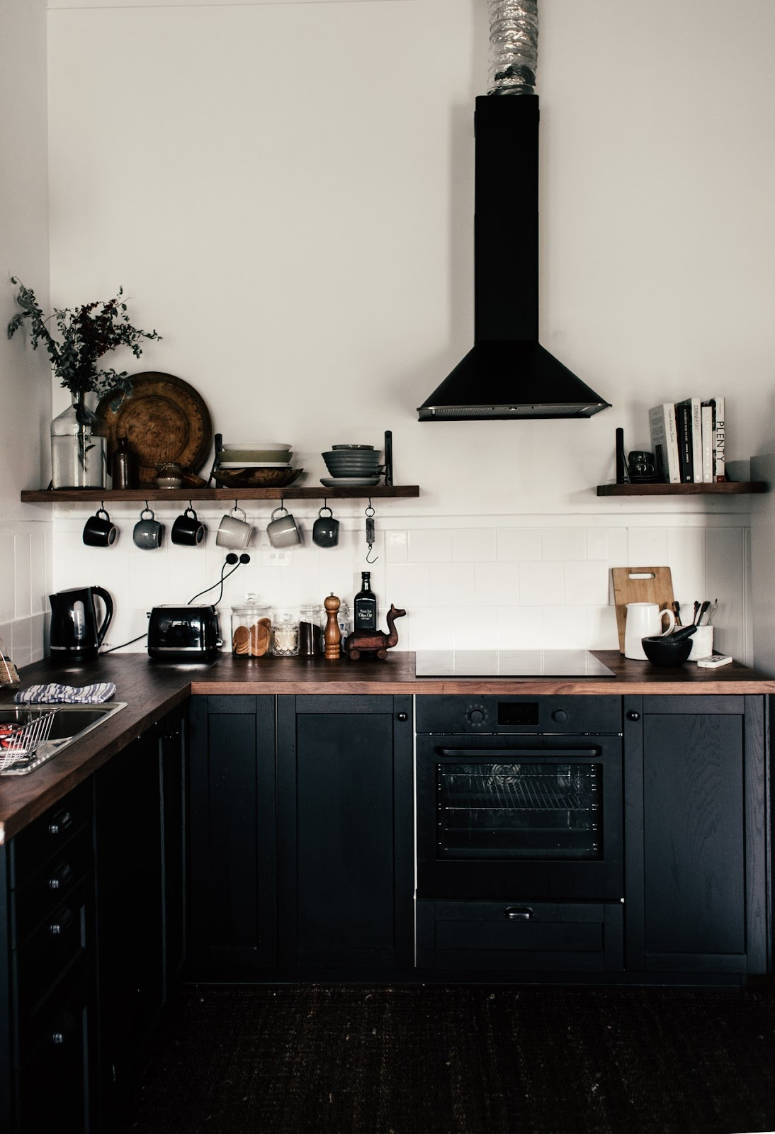 Black Open Cabinet Design suit every kitchen; wooden planks fitted on walls with kitchen cookware and decor.