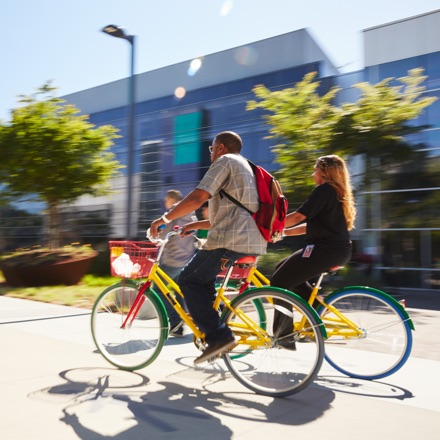 A man and a woman riding green and yellow Google bikes on Google's campus