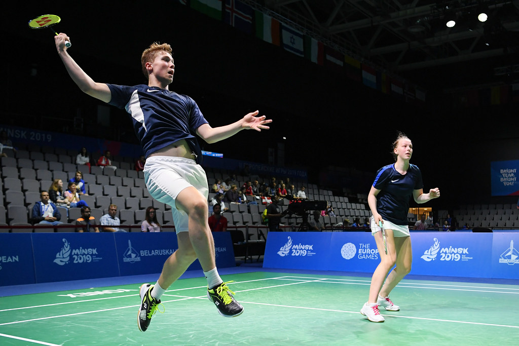 A man and a woman participate in a competitive mixed doubles game.  The man is airborne with his racket held high, prepared to connect with an oncoming shuttlecock.