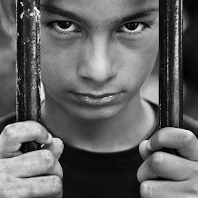 Imprison innocence... by Elias Spiliotis - Babies & Children Child Portraits ( look, face, loneliness, sadness, black and white, sad, people, portrait, eyes, prison, hands, emotions, boy,  )