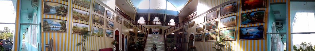 Photo: The lobby of the hotel. Paintings of European-style architecture and landscape on the left wall and Filipino-inspired paintings on the right wall.
