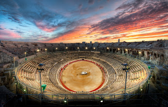 Photo: The Gladiator Arena at Sunset  While visiting Fabien in Nimes, there was a bullfight going on inside this ancient Roman gladiator arena.  The further south you go in France, the more likely you are to find the old influence of the Spanish bullfights.  It's pretty violent, yes?  Yes.  In fact, if you zoom in, you can still see blood that has been smeared across the arena by the smearing-truck.  Once the crowd started to clear out, a perfect sunset settled upon us.  It was just Fabien, my wife, and I, and it was a very nice night.  After the bullfight, we walked around to take a lot of photos of this amazing evening, Fabien took us to his favorite little secret French restaurant down one of the side streets.  Perfect!  from the blog www.stuckincustoms.com