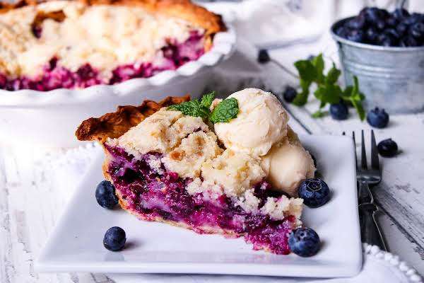 A Slice Of Blue Berry Cream Pie With Two Scoops Of Ice Cream.