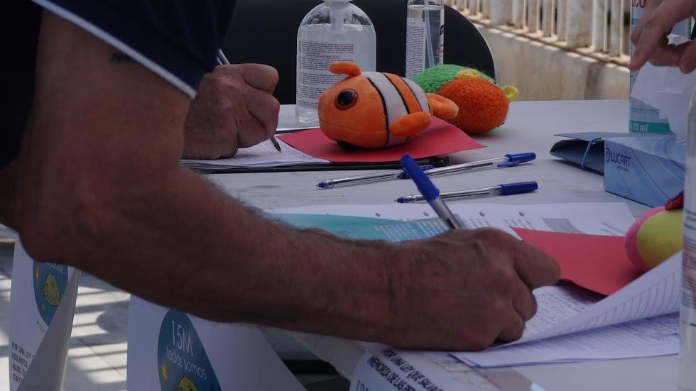 Detalle de un hombre firmando con un peluche de Nemo en la mesa