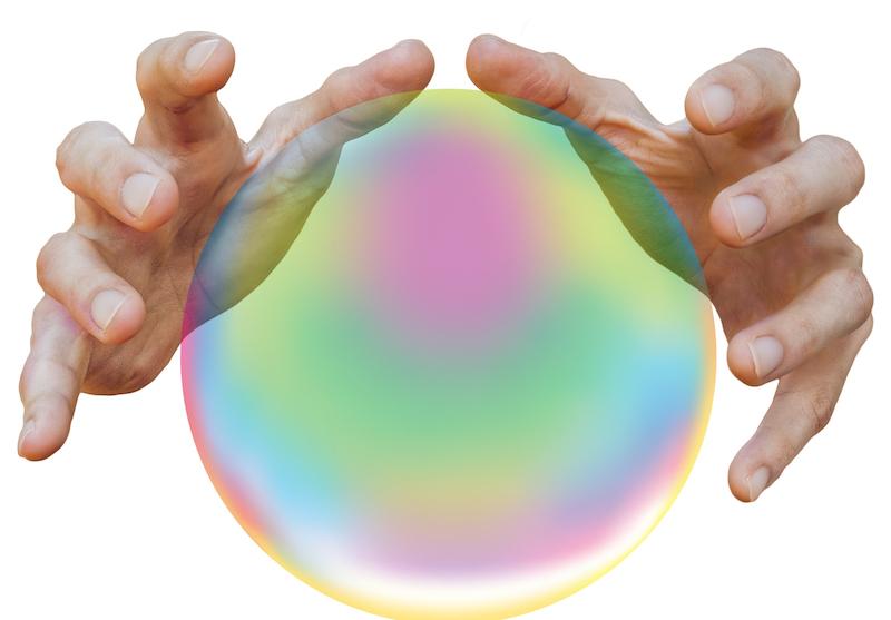 Par de mãos sobre uma bola de cristal.