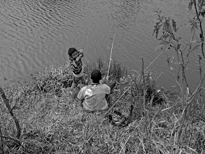 Photo: A shy young boy smiles up at me through his hands, while his friend continues to fish in a small river by the assentamento.