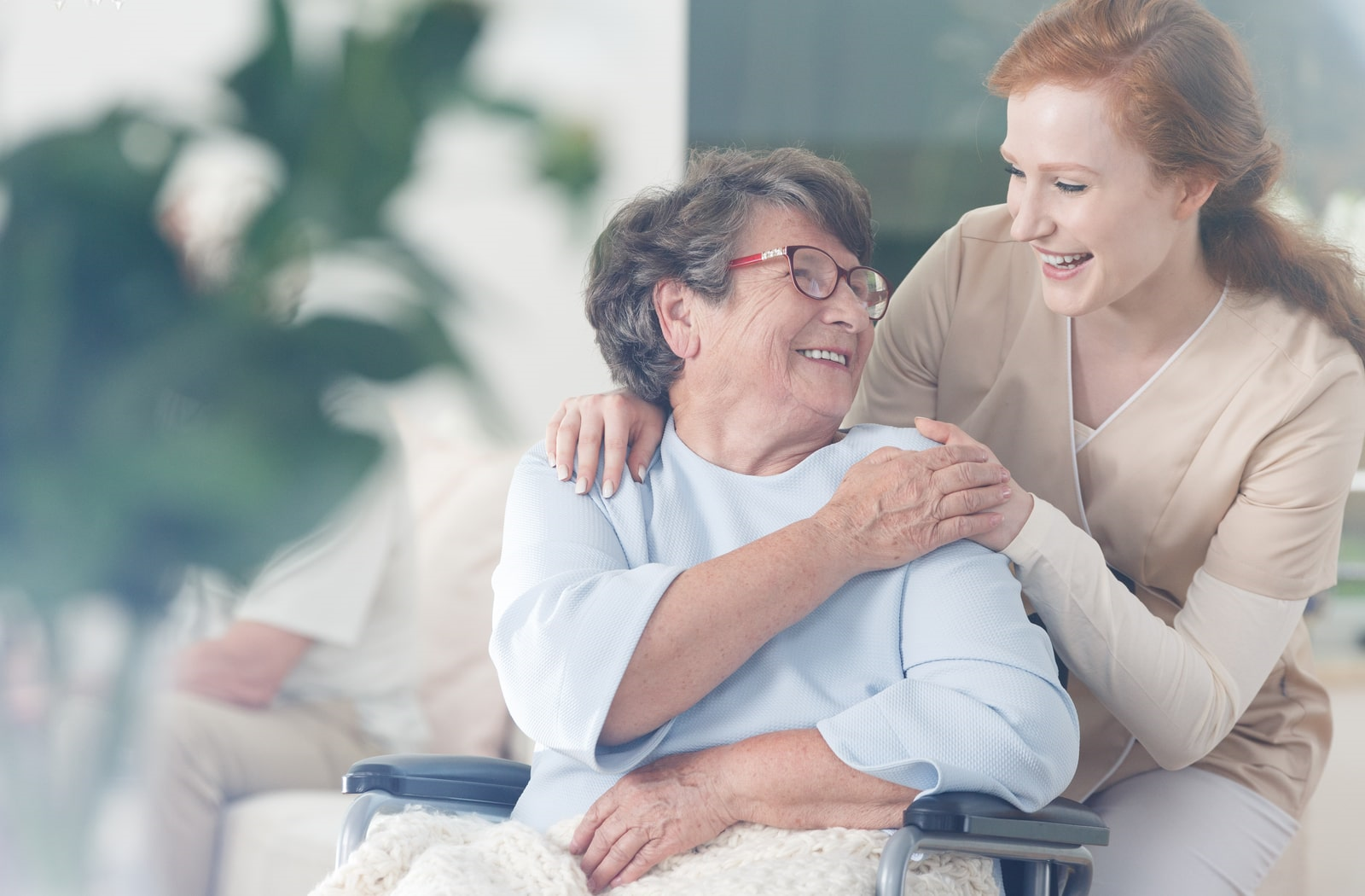Happy woman receiving personalized care from an attendant at her assisted living community