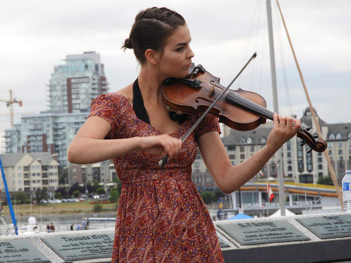 A street performer plays the violin for spectators along the waterfront in Victoria, British Columbia.