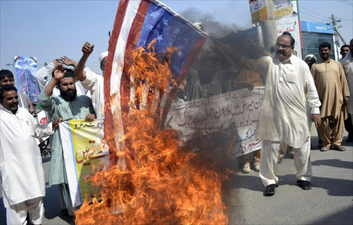 A Pakistani United Citizen Action demonstrator holds a burning US flag during a protest in Multan on October 25, 2012 against the US drone attacks in Pakistani tribal areas. File photo.