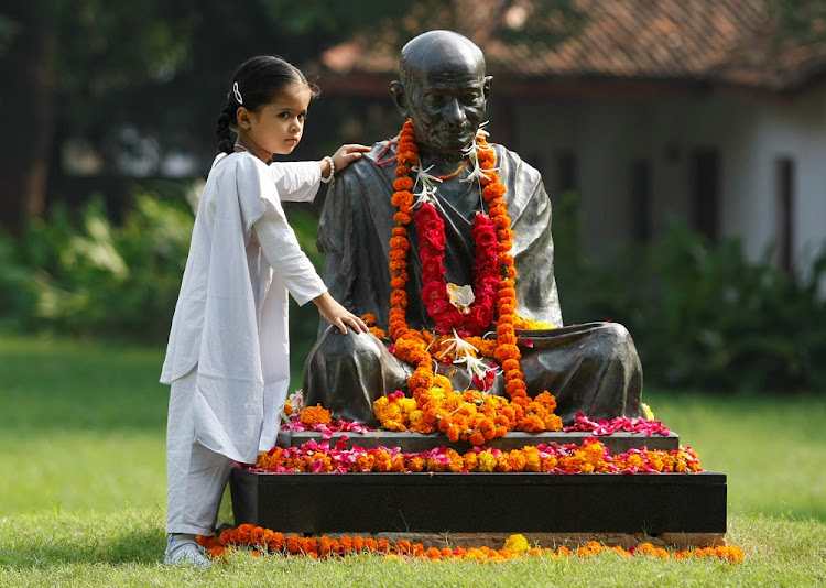 A schoolgirl stands next to a statue of Mahatma Gandhi in Gujarat, India. Picture: REUTERS