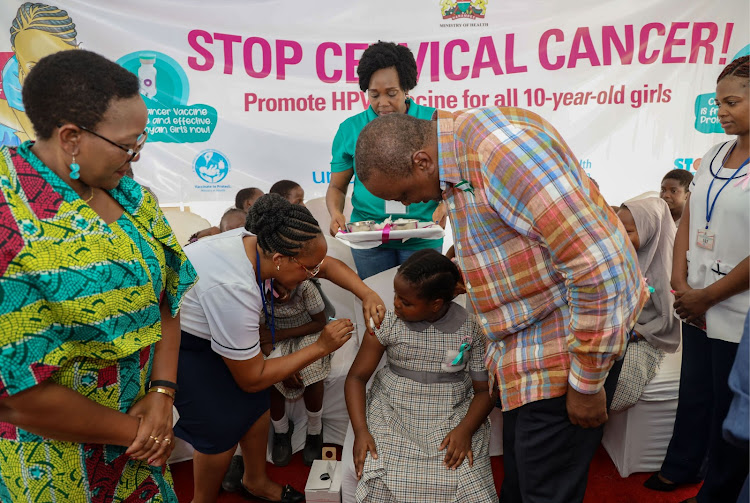 Health CS Sicily Kariuki and President Uhuru Kenyatta look on as the HPV vaccine is administered to a 10-year-old girl during the groundbreaking national launch at Ziwani Primary, Mombasa county, last year.