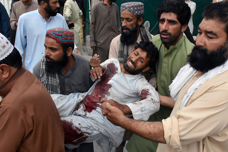 Men move an injured man after a suicide attack during an election campaign meeting, outside a hospital in Quetta, Pakistan July 13, 2018.
