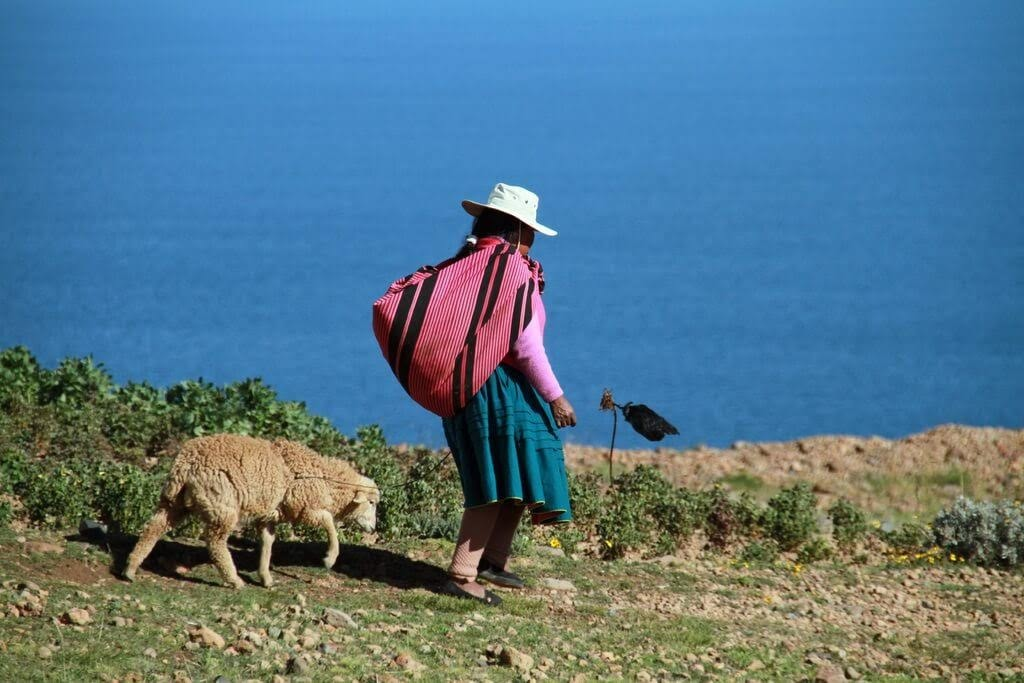 visiting lake titicaca is one of the top things to do in peru and you can see lady by the Titicaca shore here