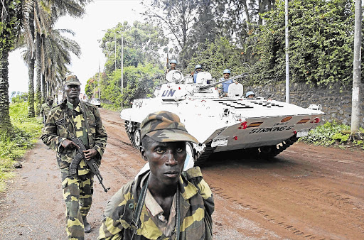 A UN peacekeepers' armoured vehicle drives past rebels patrolling a street in Goma, in the eastern Democratic Republic of Congo, soon after capturing the city from the government army.