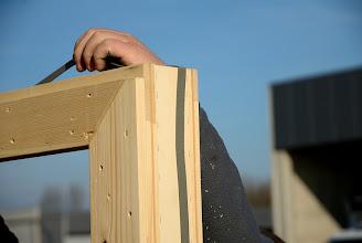 Photo: 20-11-2012 © ervanofoto Nog vlug wordt een uitzettingsband op het kader van het raam gekleefd. Deze tape is zowat drie mm dik en zal tot vijf maal uitzetten na plaatsing.