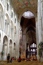 Photo: Ely Cathedral with light streaming in from three tiers of arched portals.