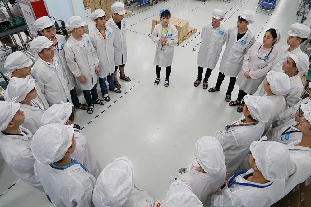 Group of factory workers standing in a circle with a manager speaking.