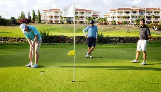 this is a picture of golfers putting on a green at barbados golf club
