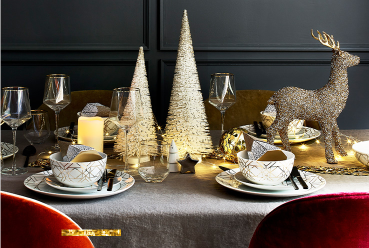 Table decorated with golden Christmas ornaments and tableware