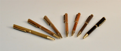 "Photo: Don Van Ryk - Slimline Pens - 5"" length - (left to right) Osage Orange, Cocobolo, Elm, Cherry, Rambutan, Walnut, Ebony"