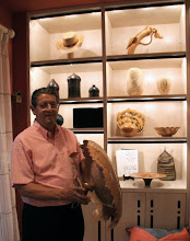 Photo: Jerry Kaplan holding a large, stemmed burl bowl by Chris Ramsey. Behind him are works by Johannes Michelsen, Michelle Holzapfel, Richard Raffan, David Ellsworth, Jerry himself, John Jordan, Mike Mahoney, Mindy Fawver, Phil Brown, and others