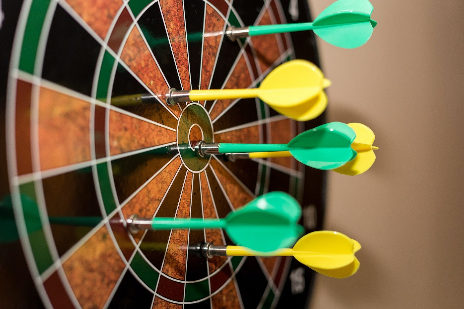 Darts cover a target in a wide spread.