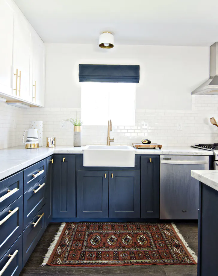 navy blue shaker cabinets are installed in the base of the kitchen, with white shaker cabinets on top. a glossy white subway tile backsplash reflects the natural light from the sink window