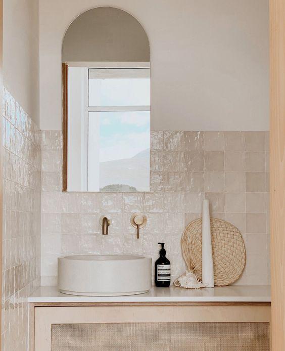 Banheiro com azulejos neutro em meia parede, mobília neutra e cuba branca