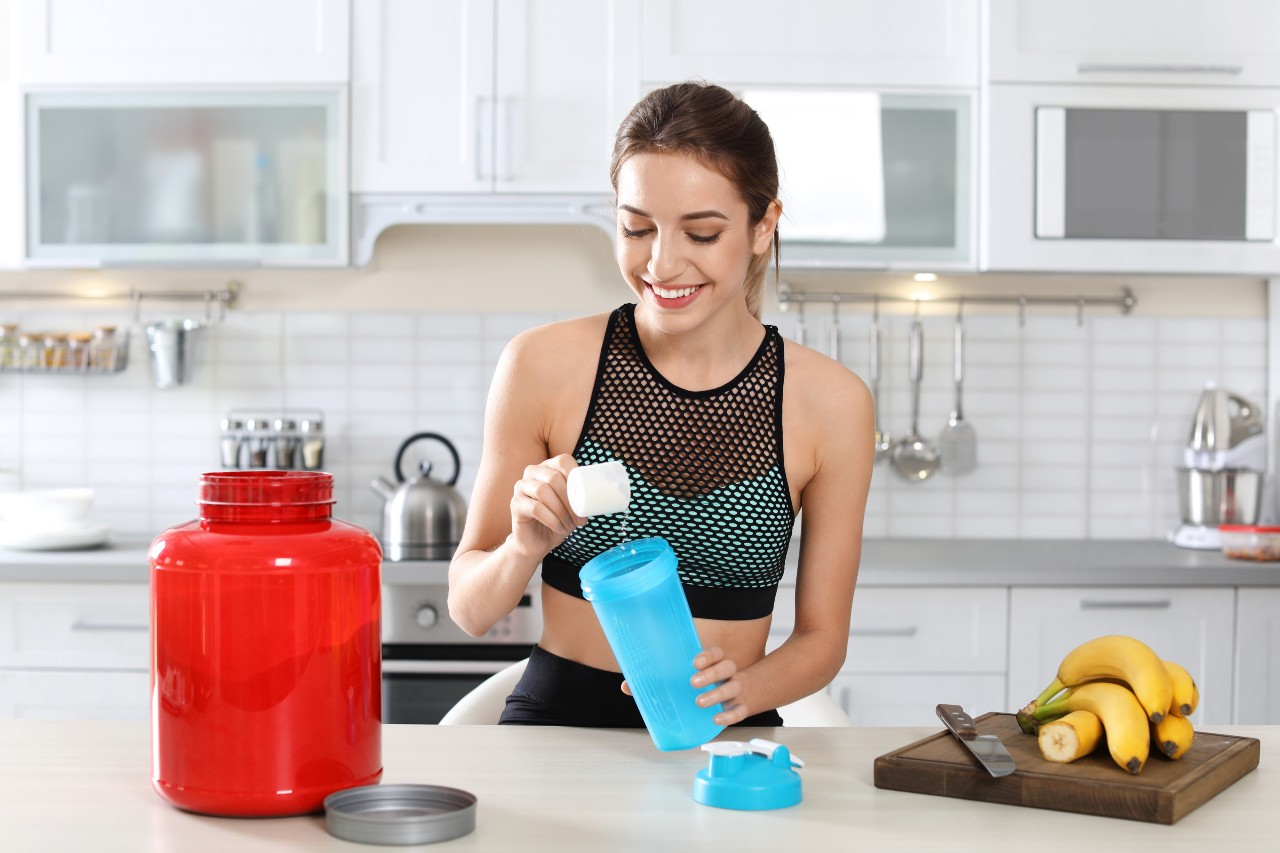 Woman adding protein powder to a shaker bottle
