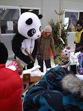 Photo: Panda mascot helping children manufacture bamboo skis.  Really.