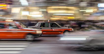 Photo: A taxi cab zooms through Shibuya Crossing
