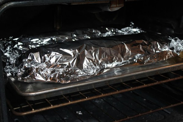 Bread covered in aluminum foil in oven.