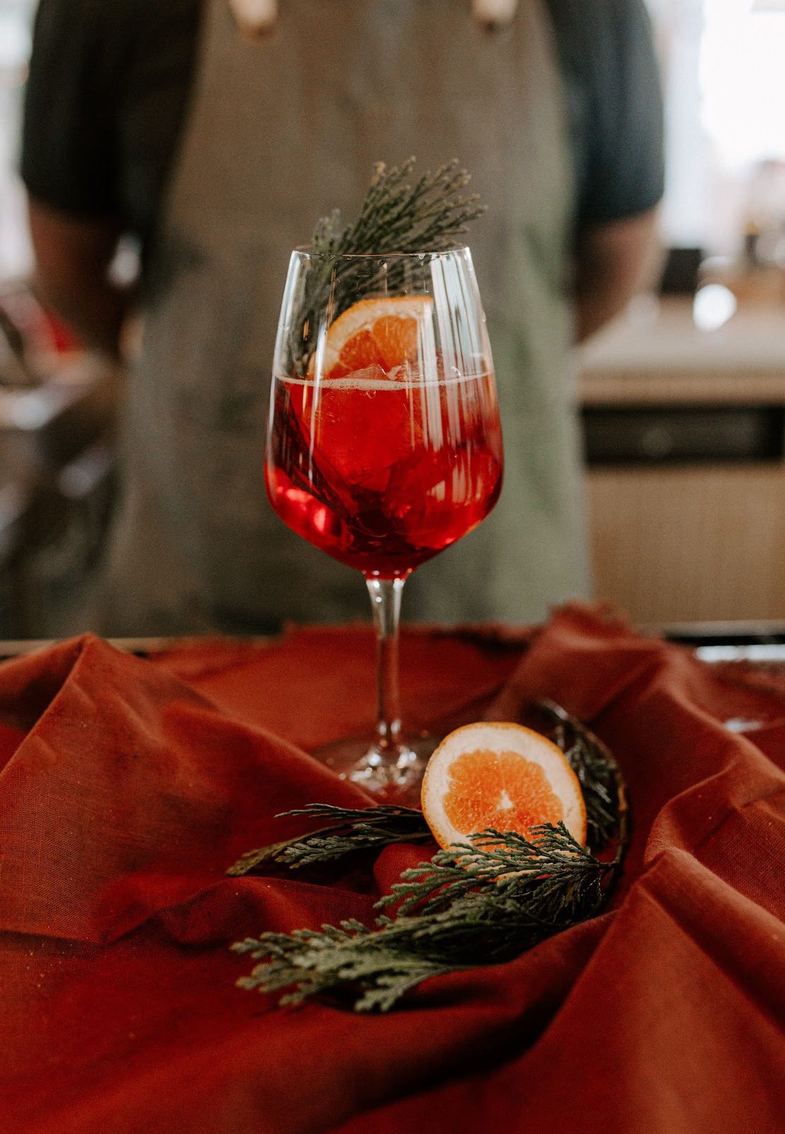 Beautiful stemmed wineglass with amber colored alcoholic beverage and orange slice and cedar leaves