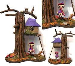 """Photo: Mueblecito multiusoso La Casa en el árbol de Nena leda (40 cm de altura, base 29x16 cm). Consta de un árbol hecho con cartón y papel  encolado y madera cuyas ramas hacen las veces de percha. La casita en el árbol es una caja de madera (8x8 cm de base y 5 cm de altura). la base y las escalera son de madera también, los detalles y las figuras de pasta de papel, el musgo es musgo para maquetas de trenes. Todo pintado en acrílico y totalmente hecho a mano. Sirve como joyero (para colgar collares, pulseras, anillos, mas la caja) o como """"pongo todo"""" (llaves..), o incluso para poner diademas y coleteros  en la habitaciónd e una niña."""