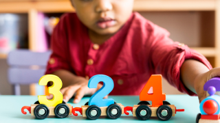 young boy playing with number blocks