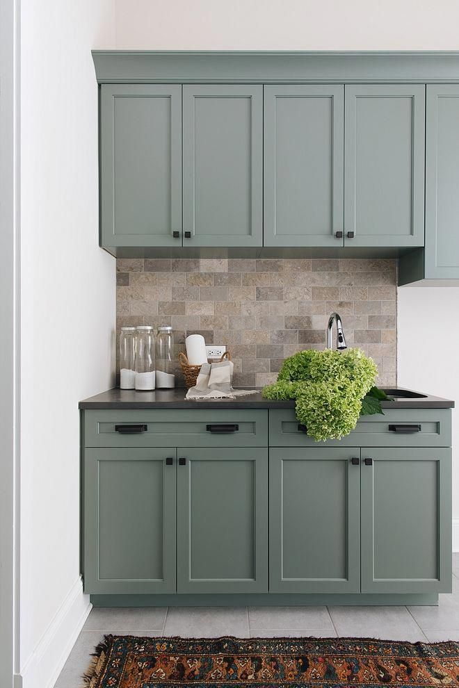 grey green kitchen cabinets with natural tile backsplash and matte black hardware