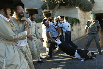 Photo: An ultra-Orthodox Jew is dragged by an Israeli police officer during a protest in Jerusalem July 25, 2009. Israeli police dragged away ultra-Orthodox men who blocked traffic outside the old walled city of Jerusalem on Saturday, in protest against a public parking lot now open on the Jewish Sabbath. REUTERS/Ammar Awad (JERUSALEM RELIGION CONFLICT IMAGES OF THE DAY)