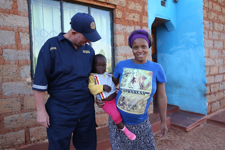 Warrant officer Jacques Meyer with two-year-old Nomfundo Mkhwanazi and her mother Sthombe on July 2, 2018.