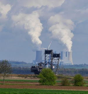 Landschaft mit Bagger, Windkraftwerk und Kohlekraftwerk.