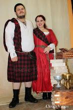 Photo: Casal escocês: Masculino: Camisa de algodão com ilhós e cordão ( Por volta de R$ 50,00), tartan e kilt em lã ( a partir de R$ 120,00), cinto e acessórios em couro e camurça. Feminino: Vestido Medieval com corset embutido em camurça e algodão ( com anágua), acabamento em gorgorão bordado ( a partir de R$ 500,00), cinto em camurça com fivela, ilhós e rebites em ouro velho ( a partir de R$ 20,00) e tartan feminino em lã ( A partir de R$ 40,00)