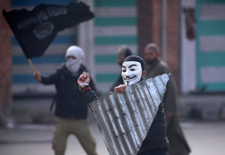 A demonstrator wearing a Guy Fawkes mask throws a stone towards the Indian police (not pictured) during a protest after Friday prayers, in Srinagar December 14, 2018.