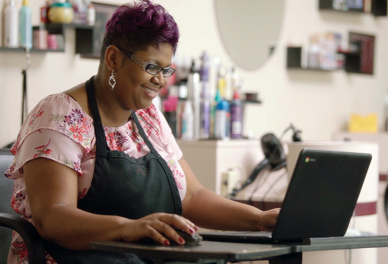 A woman wearing a black apron sits at a desk, smiling while she works on her computer.
