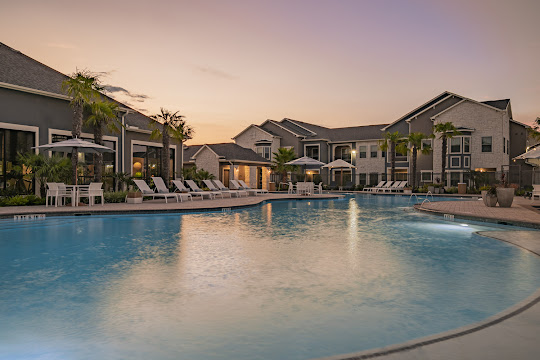 Exterior apartment building view with pool and sundeck area at dusk