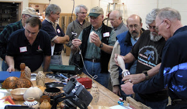 Photo: There is a lot of interest in Ed's techniques and their results, as he shows the carving chuck to Stan Sherman.